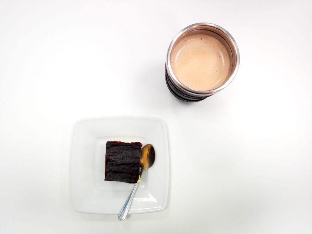 Kawa z mlekiem w kubku i ciasto na talerzyku obok